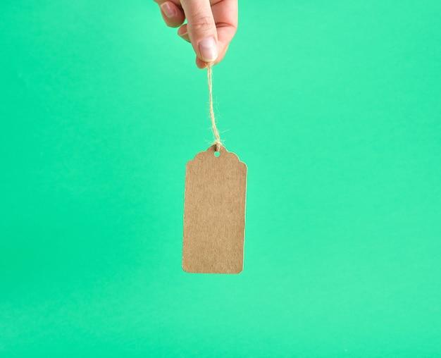 Женская рука держа бумажный коричневый пустой тег на веревке