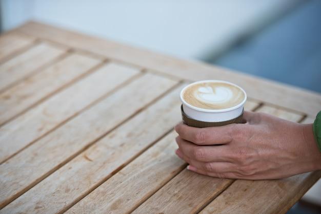 Женская рука держит бумажную чашку кофе