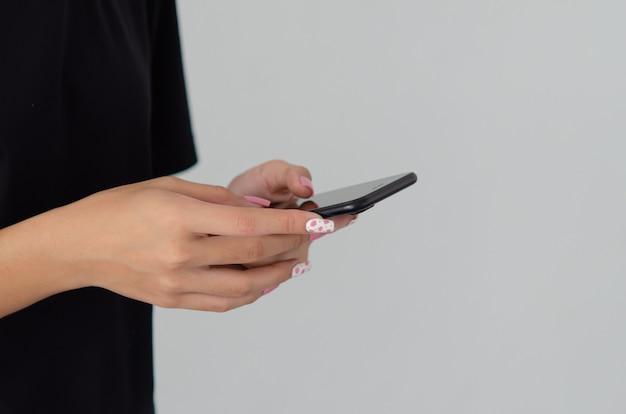 Женская рука держит телефон с красивым розовым лаком для ногтей