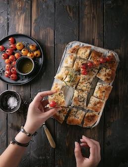 Focaccia 평평한 빵 한 조각을 들고 여성 손은 구운 토마토, 올리브 오일, 신선한 로즈마리, 빈티지 냅킨 및 나이프와 함께 나무 배경 위에 제공됩니다. 평면도