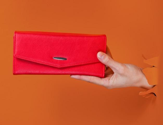 찢어진 된 주황색 종이 통해 빨간색 지갑을 들고 여성 손. 미니멀리즘 창의적인 패션 컨셉