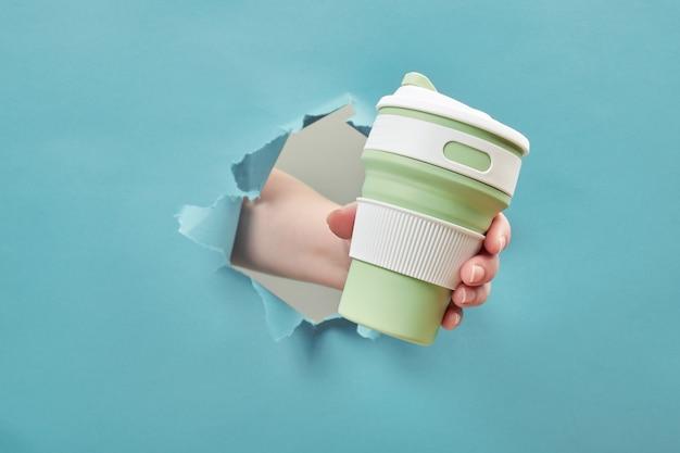 Женская рука силиконовая многоразовая чашка через разорванное отверстие.