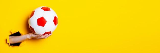Женская рука держит футбольный мяч с красно-белым на ярко-желтом фоне