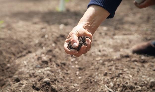 Женская рука, держащая почву в поле.