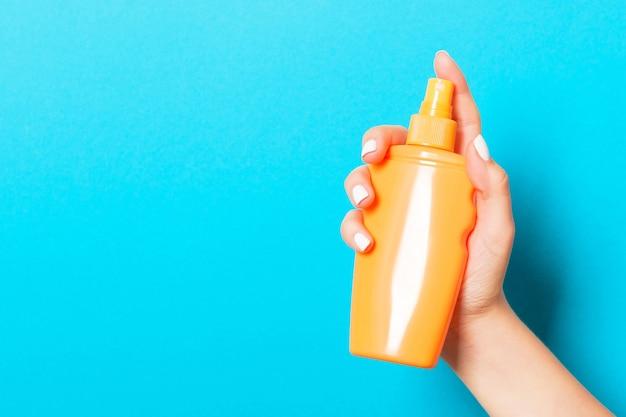 Женская рука, держащая спрей косметического продукта на синем фоне с пустым пространством для вашего дизайна.