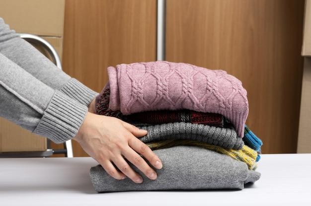 服のスタック、ヘルプ、ボランティアの概念を持っている女性の手。物事を分類する