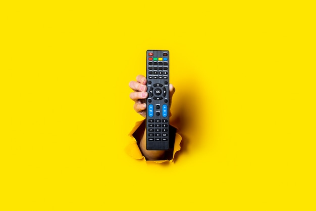 明るい黄色の背景にテレビのリモコンを持っている女性の手