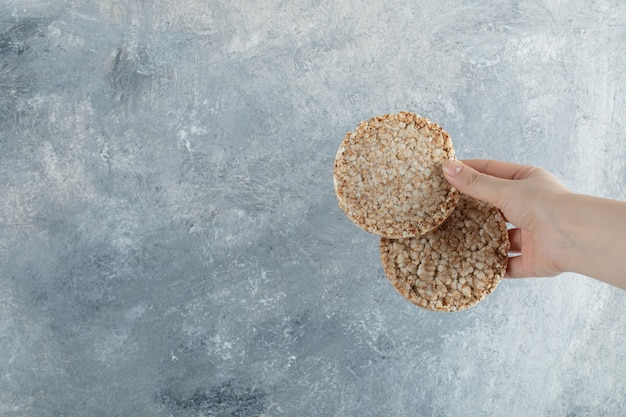 Female hand holding airy crispbread on marble surface
