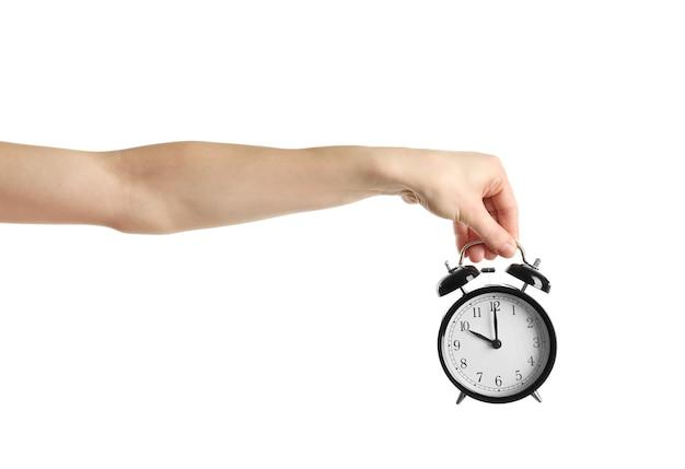 흰색 표면에 알람 시계를 들고 여성 손