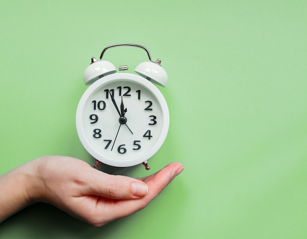Female hand holding an alarm clock on pastel green background.