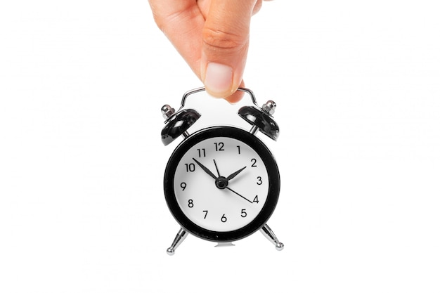 Female hand holding alarm clock on white