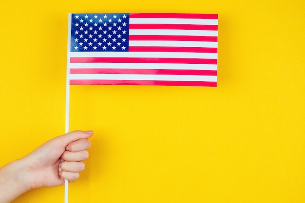 Female hand holding an american flag on a yellow background. concept of the independence day of america july 4.