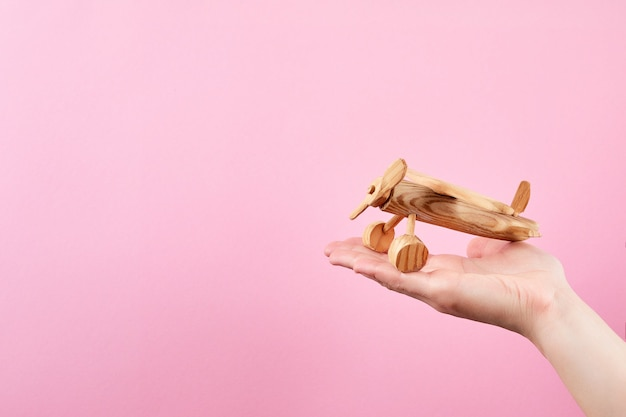 Женская рука держит самолет на пастельно-розовом фоне. деревянный рубанок ручной работы.
