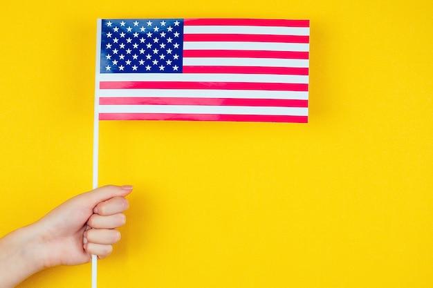 Женская рука держит американский флаг на желтом фоне. концепция дня независимости америки 4 июля.