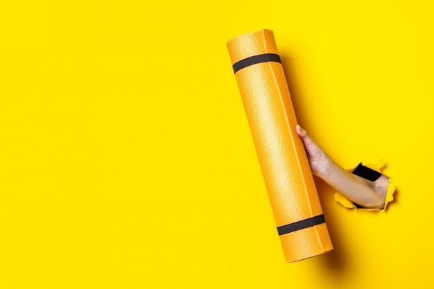 明るい黄色の背景にオレンジ色のヨガマットを持っている女性の手