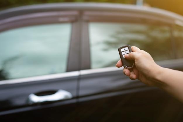 車のリモコンを持って押して車をロックまたはロック解除する女性の手。