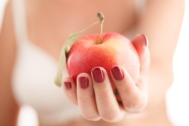 Female hand holding an apple