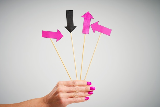 A female hand holding arrows over grey background