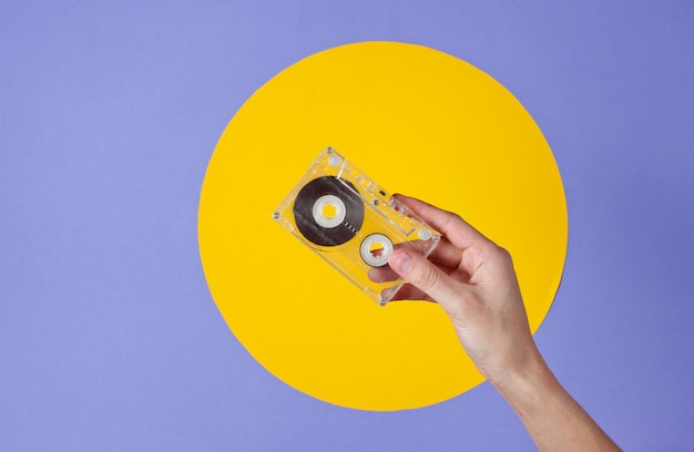 Female hand holding audio cassette on purple with yellow circle
