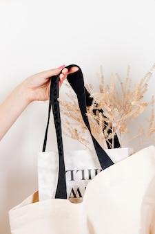 Женская рука держит сумку для журналов, макет многоразового белого хлопкового экосумки с сухими цветами, лежащими в ...