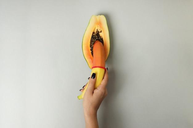 Женская рука держит банан с презервативом в папайе на светло-сером фоне