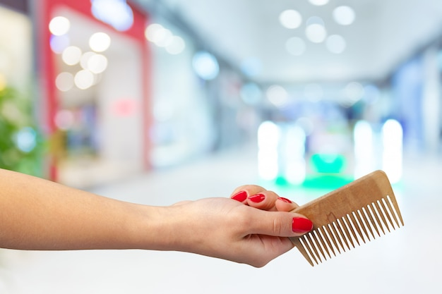 Female hand holding barber comb in cosmetic store