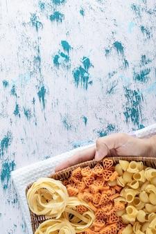 Женская рука, держащая корзину с сухими макаронными изделиями на красочном фоне. фото высокого качества