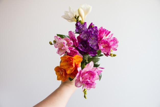 Mano femminile che tiene un bellissimo bouquet di fiori colorati