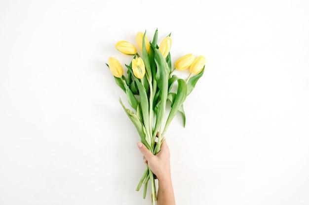 화이트에 아름 다운 노란 튤립 꽃 꽃다발을 들고 여성 손