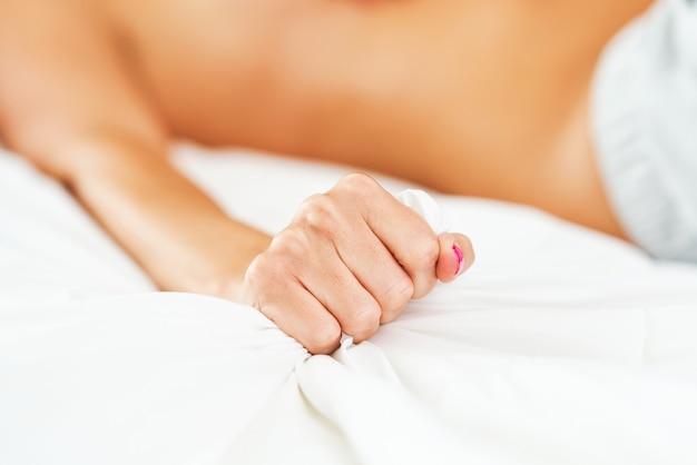 여성의 손을 잡고 침대 시트