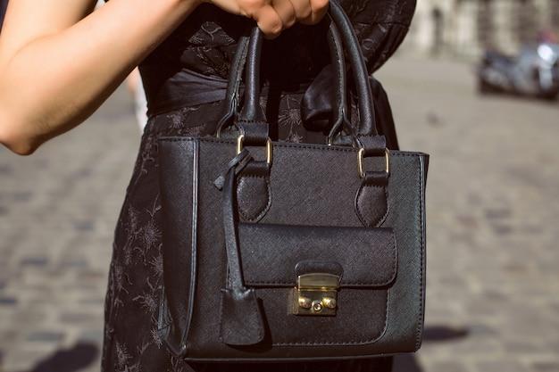 街の背景に黒い革の財布を持っている女性の手。クローズアップショット