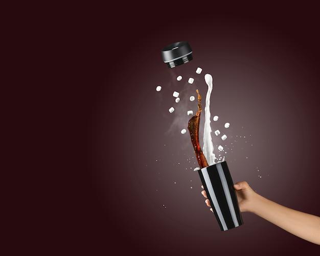 Женская рука держит термоблок из черного металла на темно-коричневом фоне с горячим брызгом кофе и молока