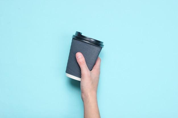 Женская рука держа черный бумажный контейнер кофе на голубой пастели. вид сверху.