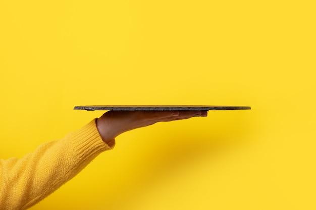 Женская рука держит черную грифельную доску над желтым