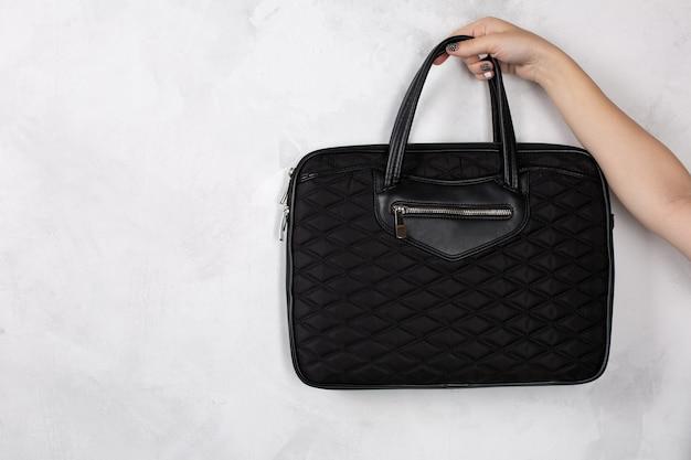 黒のテキスタイルノートブックハンドバッグを持っている女性の手。空きスペース