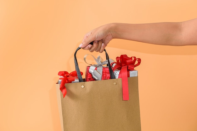 Female hand holding blank brown papaer shopping bags full of gift boxes ornamented