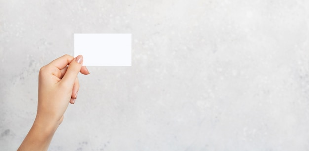 Female hand holding a blank business card, cutaway on gray concrete background with copy space. branding mockup template.