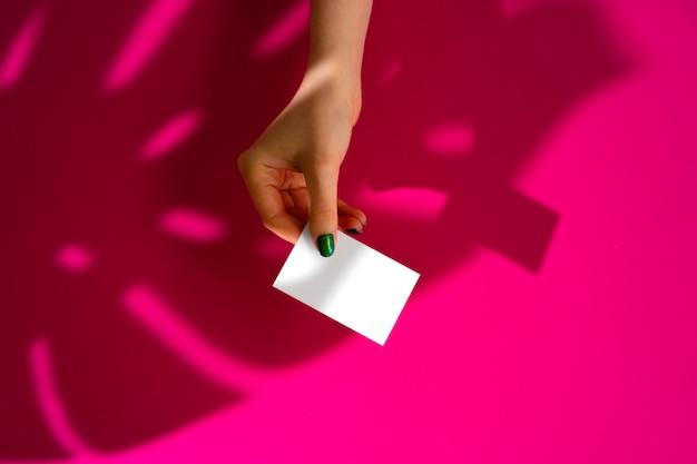 Женская рука держит пустой визитка. креативное фото с тенью