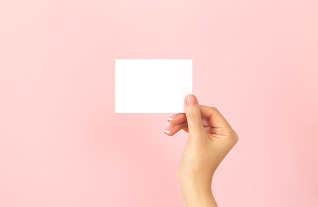 Female hand holding blank white business card, discount or flyer on pink background