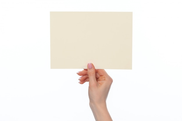 Женская рука держит чистый белый лист бумаги на белом