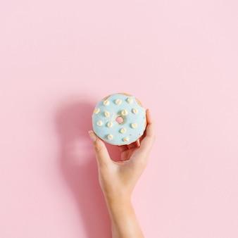 Женская рука держит голубой пончик на пастельно-розовом фоне