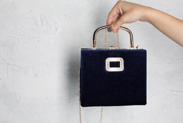 白い背景の上に金色のチェーンと青い革のハンドバッグを持っている女性の手。テキスト用のスペース