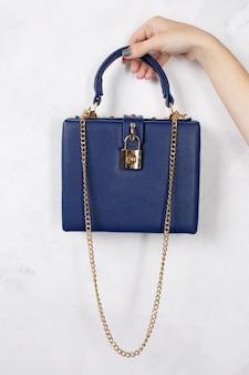 白い背景の上に金色のチェーンと青い革のハンドバッグを持っている女性の手