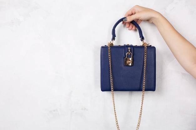 金色のチェーンと青い革の財布を持っている女性の手。テキスト用のスペース