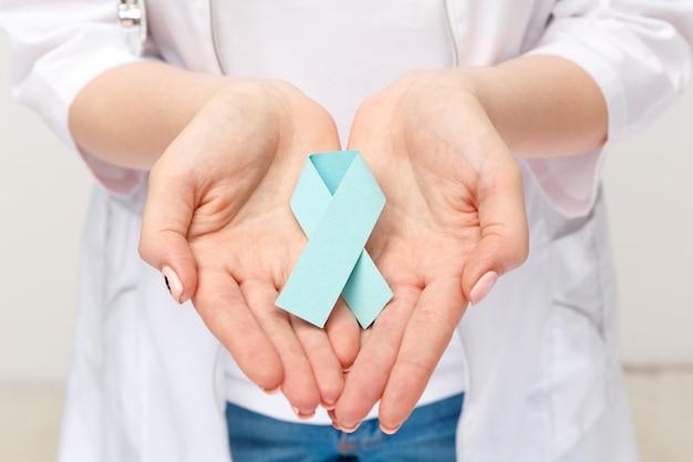 Женская рука, держащая голубую ленту изолирована.