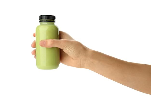 白のアボカドスムージーのボトルを持っている女性の手