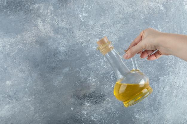 灰色の背景に植物油のボトルを持っている女性の手。