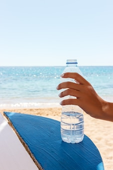 Female hand holding a bottle of water on the beach, sea background