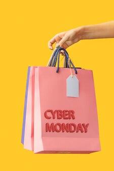 노란색에 밝은 쇼핑백을 들고 여성 손입니다. 사이버 먼데이 및 판매 개념