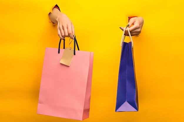 찢어진 종이를 통해 노란색에 밝은 쇼핑백을 들고 있는 여성 손